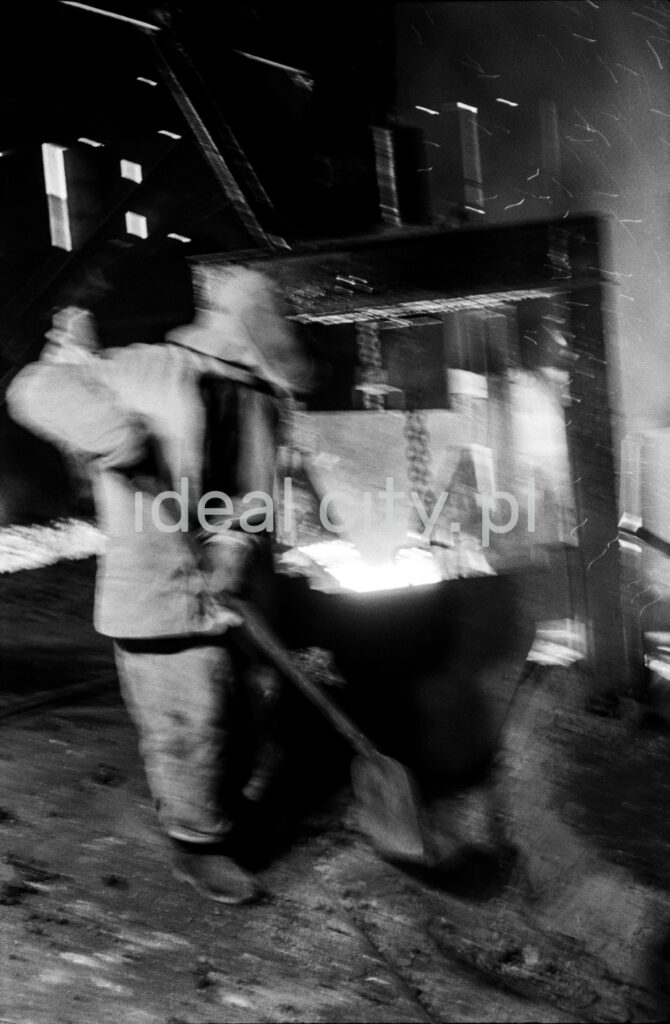 A steelworker in a full outfit cleans up the furnace surroundings with a shovel.