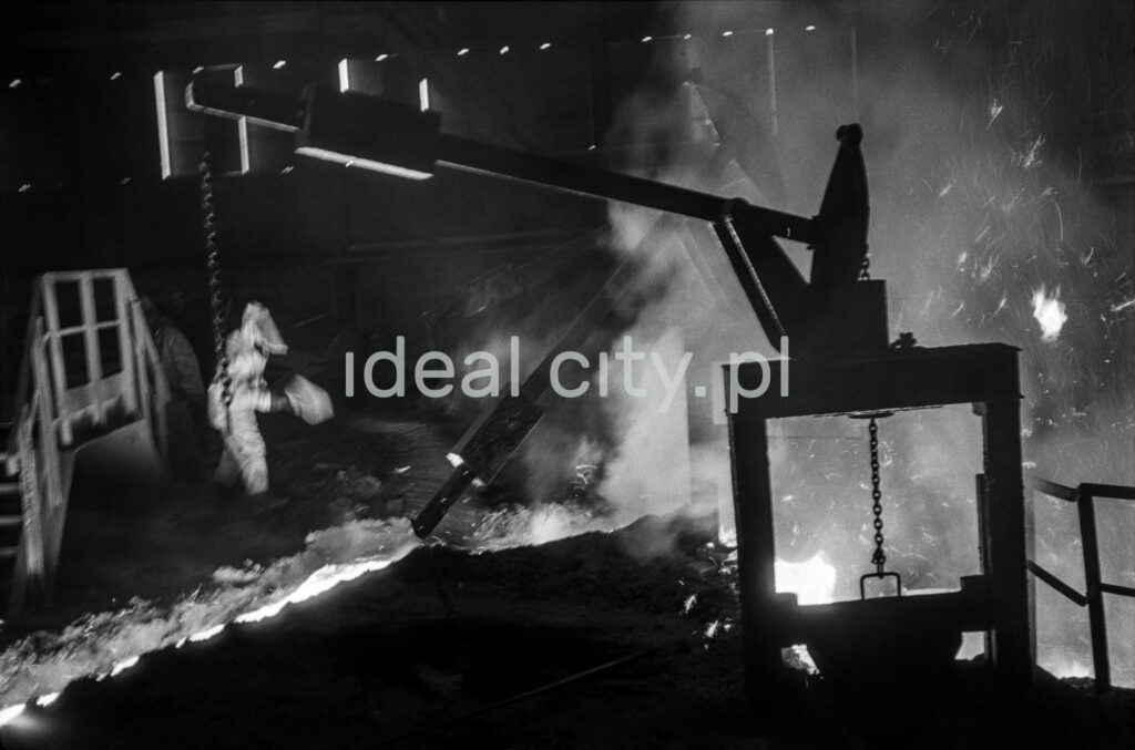 A steelworker in full outfit controls a stream of molten pig iron with a shovel.