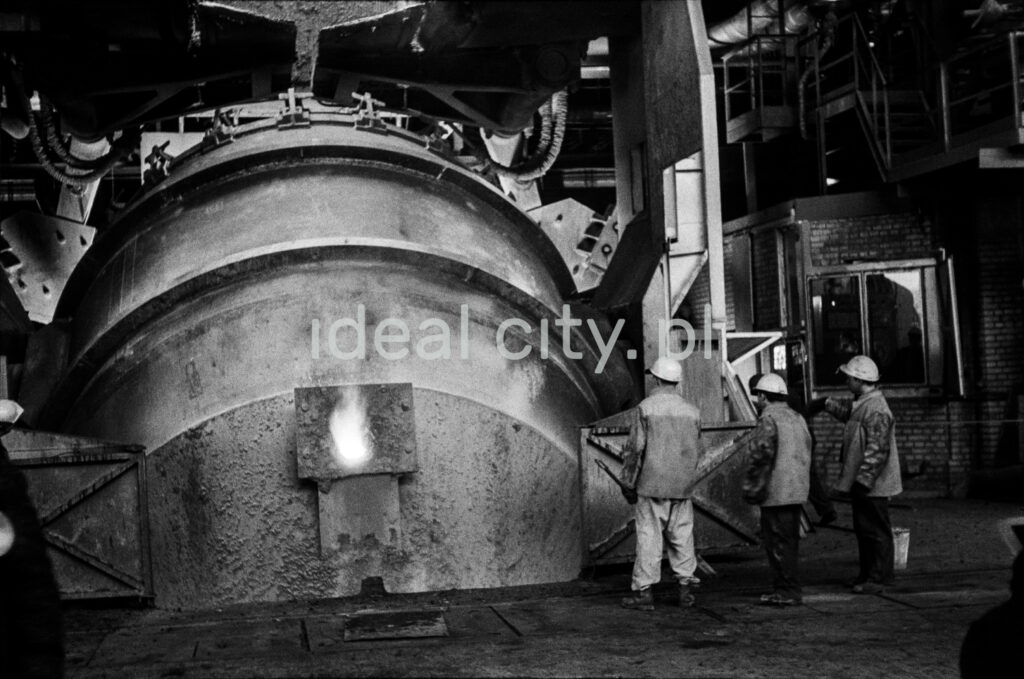 The steelworkers stand at the throat cover of the mighty furnace.