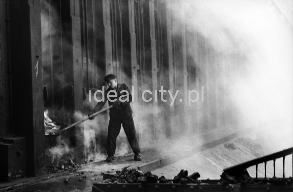 A man in work clothes uses a shovel to throw coke into a hole in a huge wall of a metal structure.