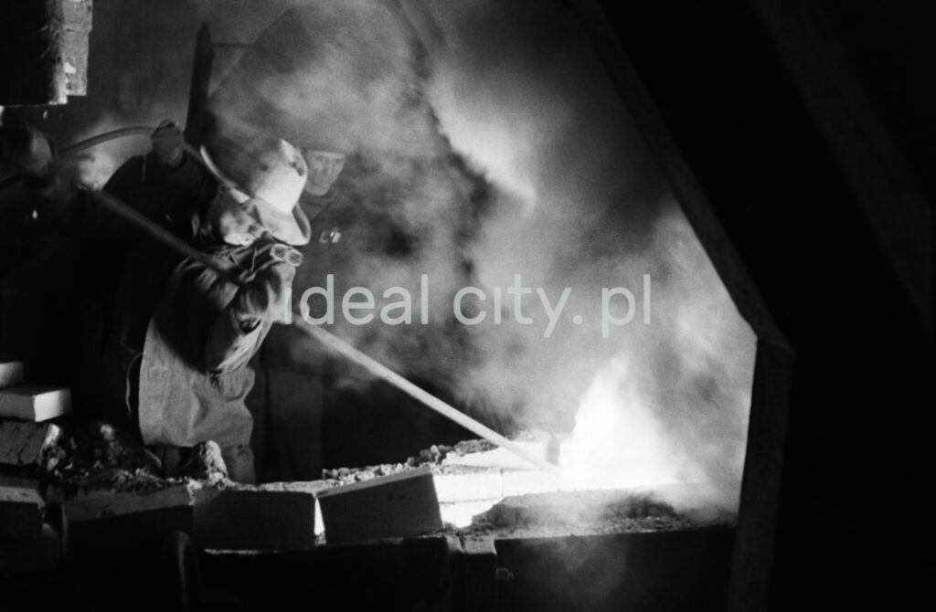 A steelworker in a costume turns a rod in a stream of flowing and smoking pig iron