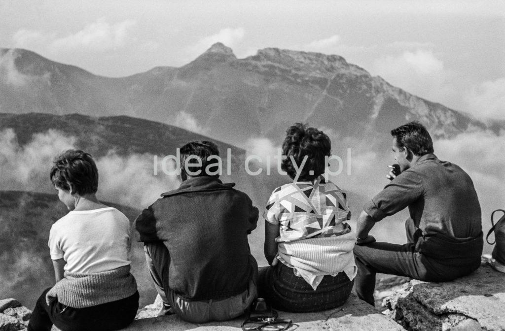 Czworo turystów odpoczywa siedząc przy jednym z wyższych szlaków, ze wzrokiem skierowanym w stronę panoramy skalistych szczytów.