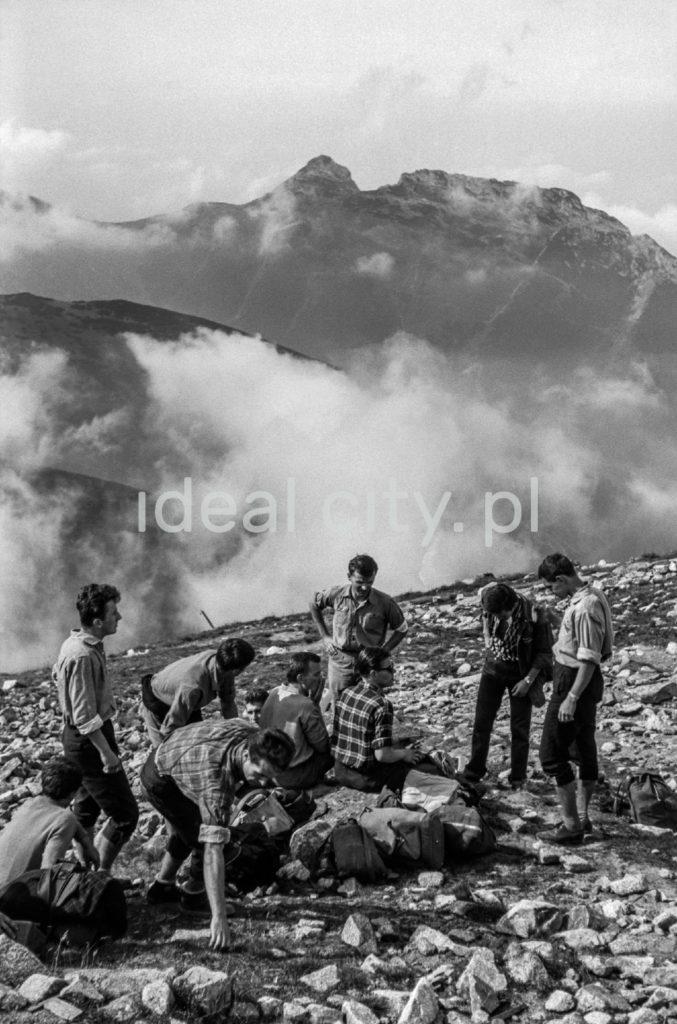Grupa turystów z plecakami odpoczywa na na szlaku, w tle panorama na dymiące szczyty górskie.