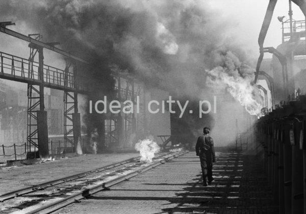 Mężczyzna w stroju roboczym idzie niespiesznie wzdłuż dymiących instalacji.