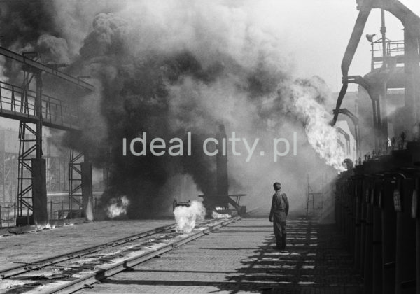 Mężczyzna w stroju roboczym stoi obok dymiących instalacji.