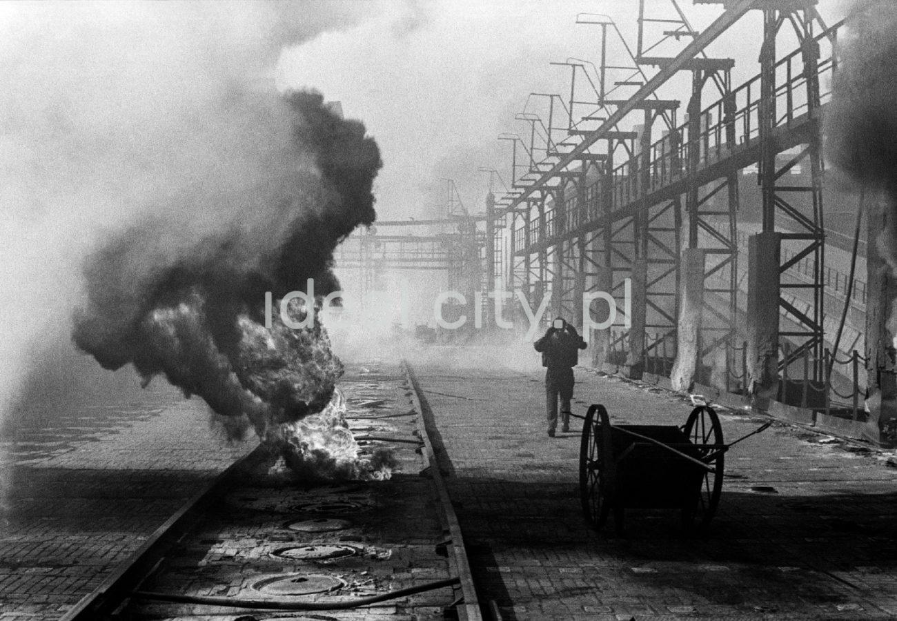 Robotnik chwyta się za głowę, stojąc pomiędzy instalacjami koksowni a płonącym na trasie suwnicy materiałem
