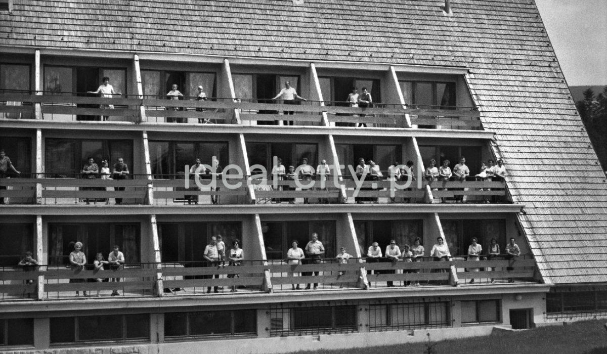 Wczasowicze na balkonach domu wczasowego o spadzistej formie.