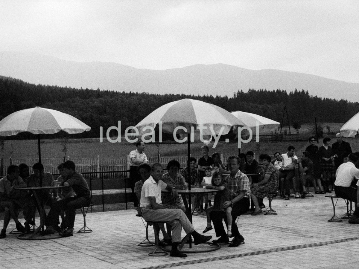 Ludzie przy stolikach pod parasolami na betonowym tarasie, w tle góry.