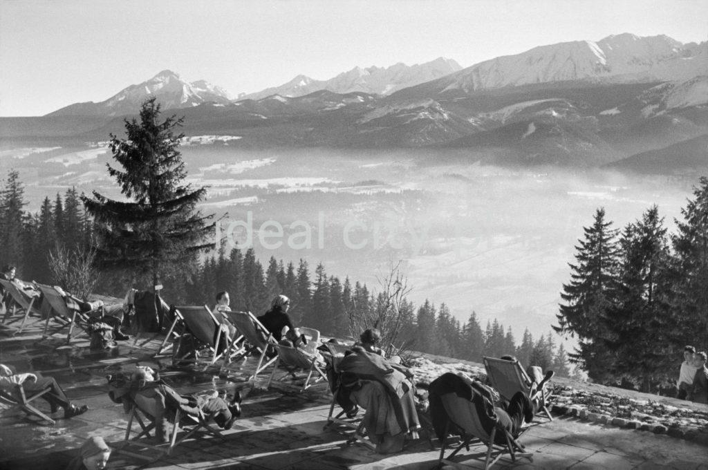 Wczasowicze na leżakach ustawionych w słoineczny dzień na ośnieżonym wzniesieniu obserwują panoramę Tatr.