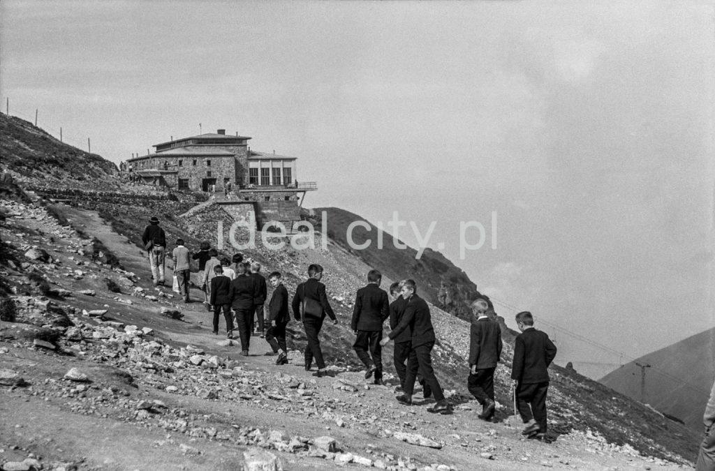 Wycieczka uczniów ubranych w garniturych dociera pieszo do schroniska na Kasprowym Wierchu.