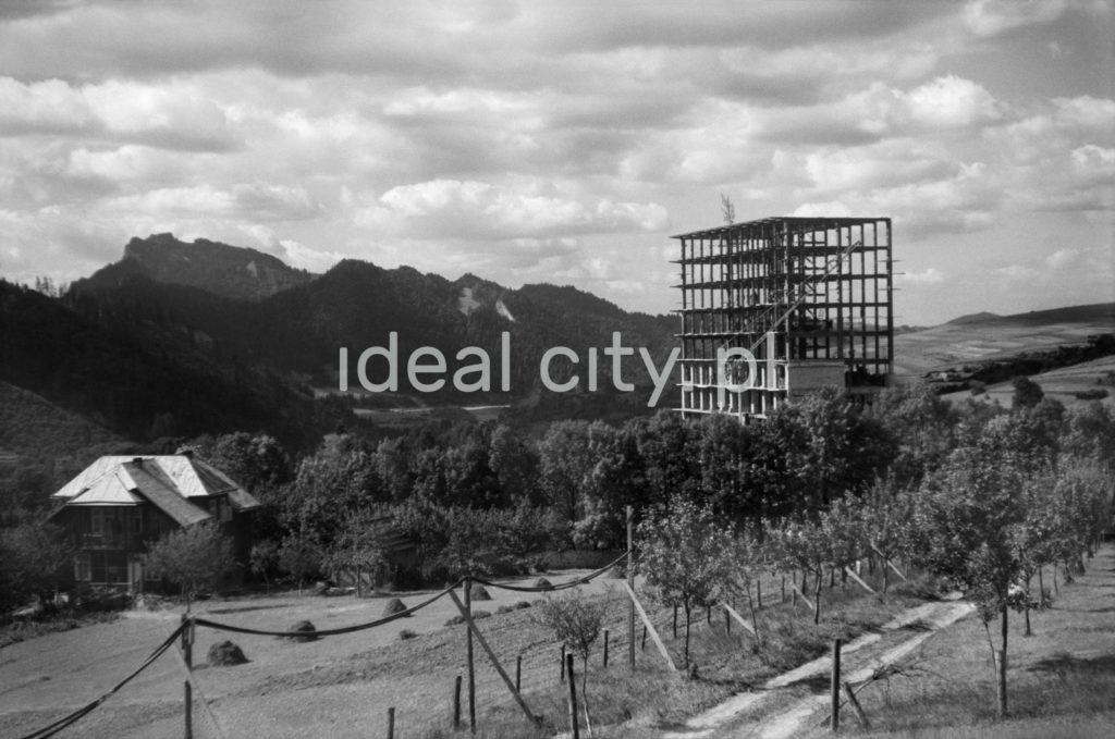Wiecha na szczycie ukończonej konstrukcji żelbetowej wysokiego budynku, jedynego w okolicy wysokościowca, w tel panaorama gór, dookoła sady.