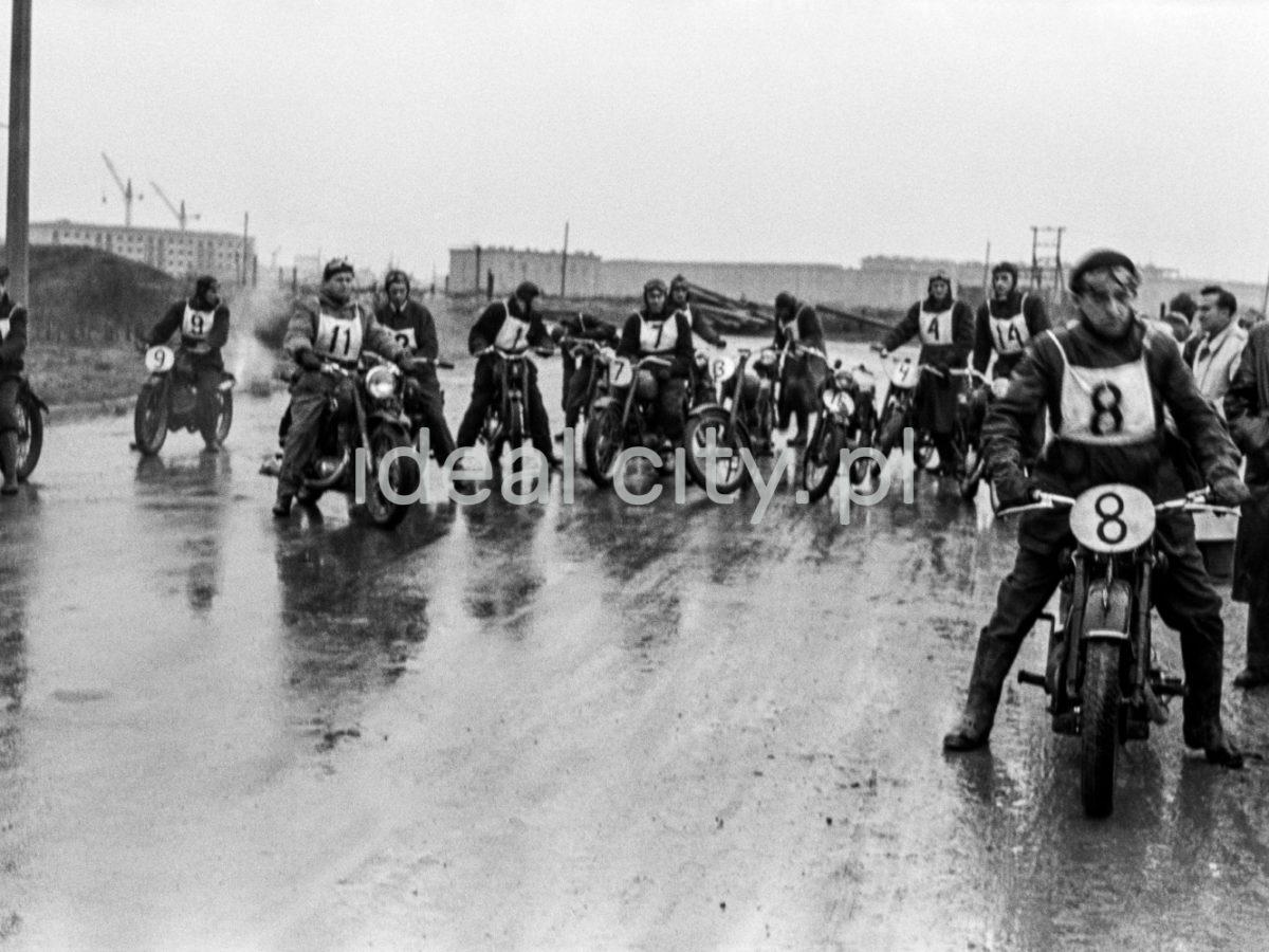 Grupa motocyklistów z numerami startowymi na mokrej drodze.