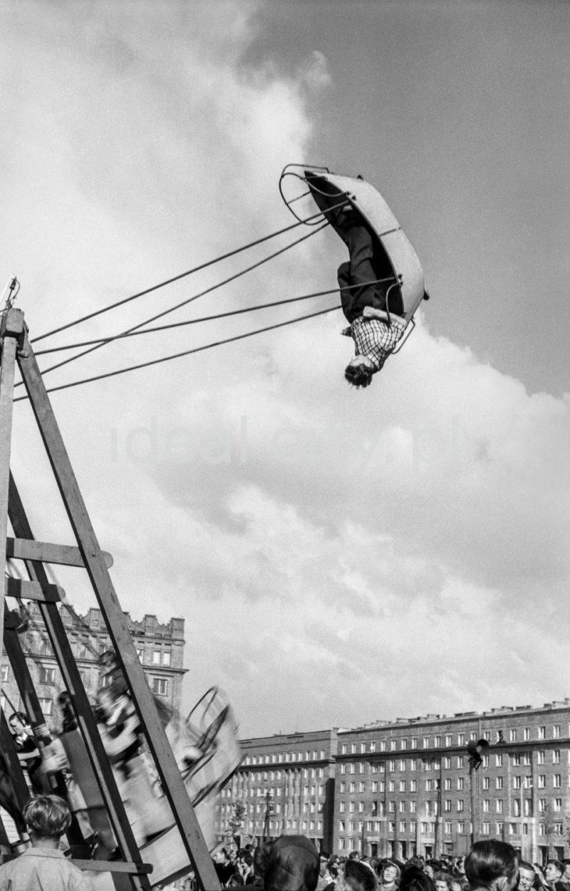 Mężczyzna do góry nogami w wychylonej do skrajnej pozycji huśtawce o kształcie łodzi, w tle budynki mieszkalne