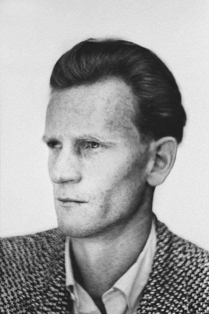 Czarno-biała fotografia w konwencji legitymacyjnej przedstawiająca mężczyznę w marynarce.