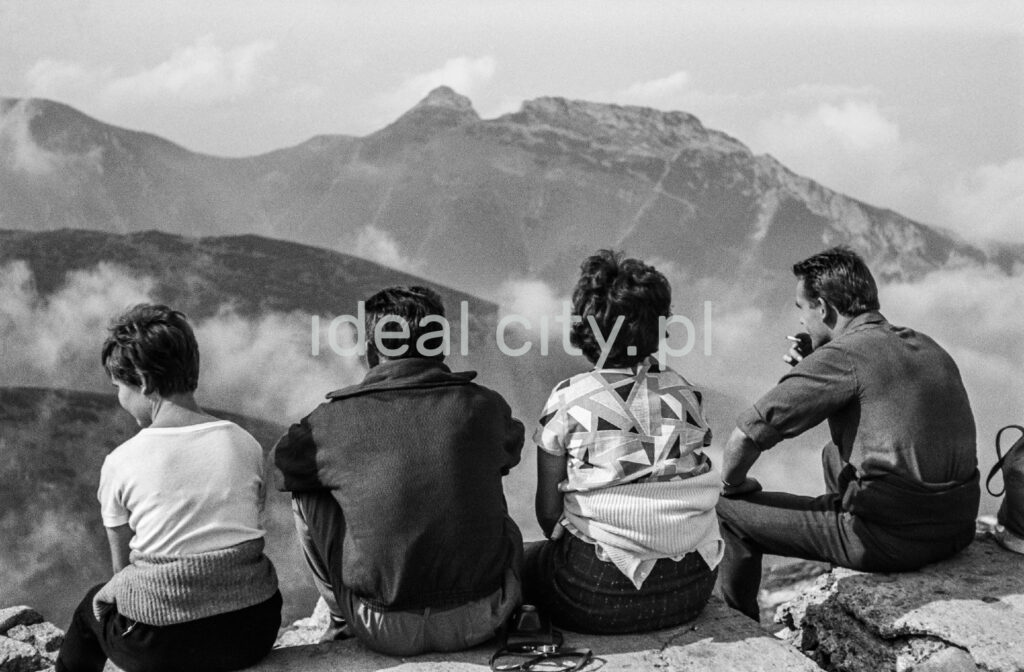 Tourists are resting on a rocky trail with a view of the Tatra peaks in the background.