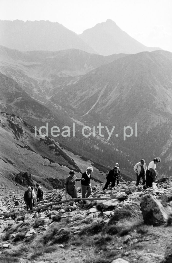 Tourists are walking along the rocky trail, with the perspective of the Tatra peaks in the background.