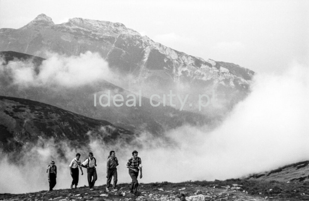 Tourists with backpacks are walking along the rocky trail, with the perspective of the Tatra peaks in the background.