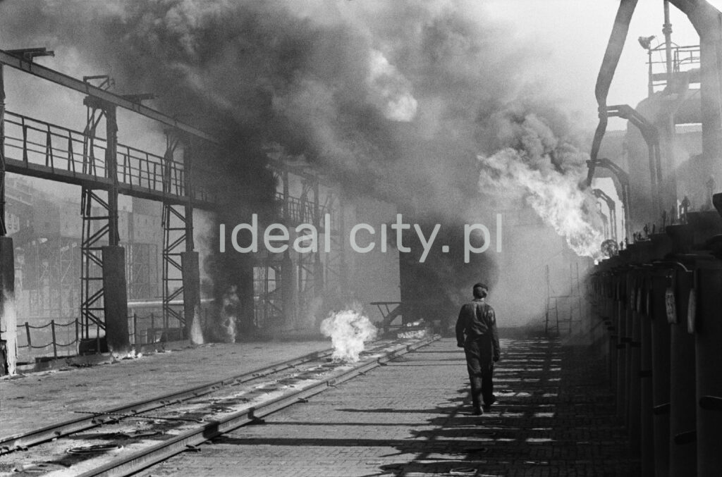 A man in workwear marches along the smoking installations of the coking plant.