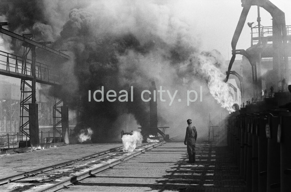A man in workwear stands in the middle of the smoking installations of the coking plant.