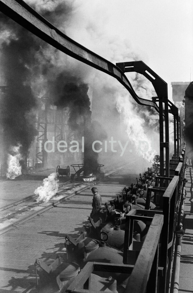 A man in workwear sits in the middle of the smoking installations of the coking plant.