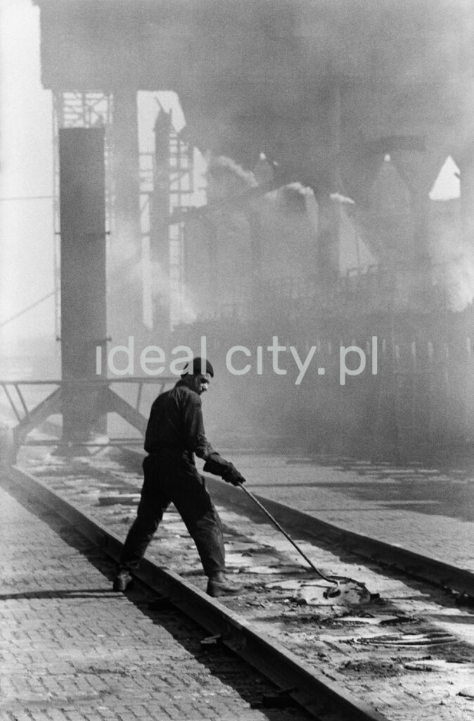A man in denim oversees the cover of the coking plant.