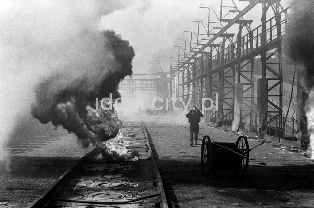 A man in denim walks through the middle of the smoking coking plant.