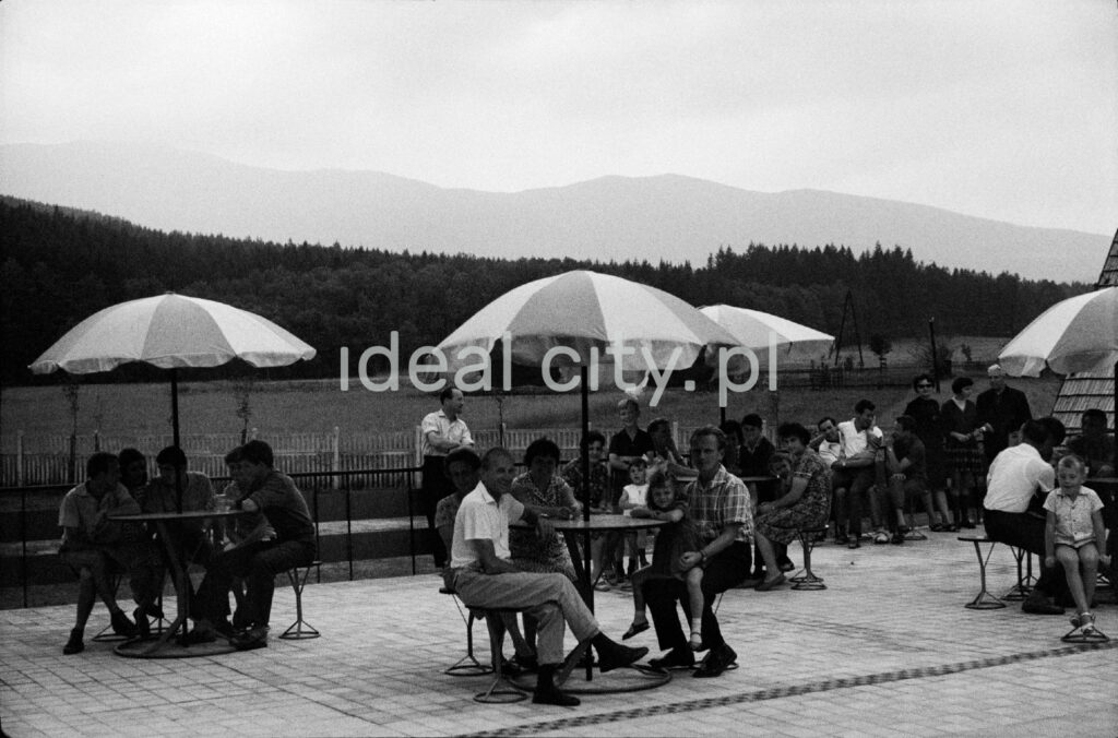 Holidaymakers sit at tables covered with umbrellas on the terrace of the holiday home.