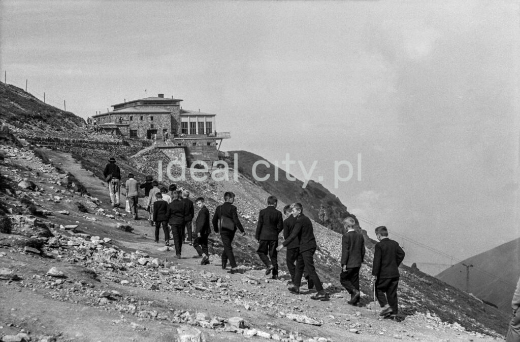 Young tourists in suits are heading towards the shelter on Kasprowy Wierch.