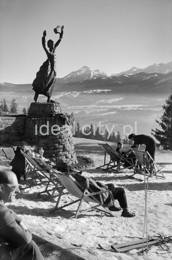 Winter patients relax in the sun on deckchairs at the top of the hill, in the background a panorama of mountain peaks.