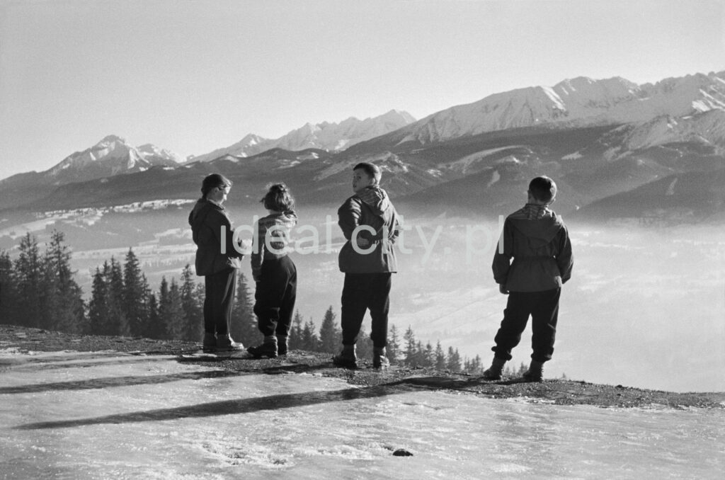 Young people watch the winter panorama of mountain peaks from the top of the hill.