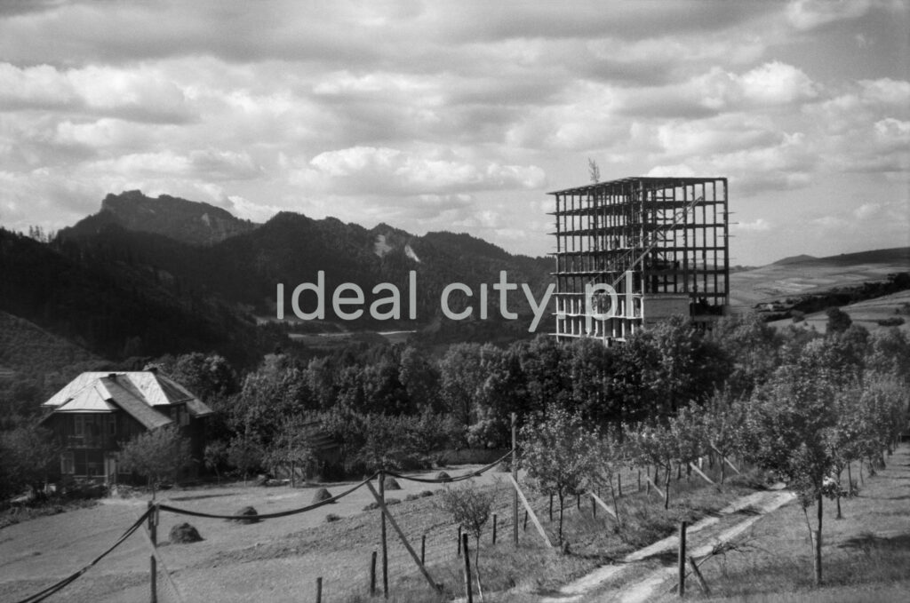 A view of the reinforced concrete skeleton of a modernist building, top floor with a panicle and mountain peaks in the background.