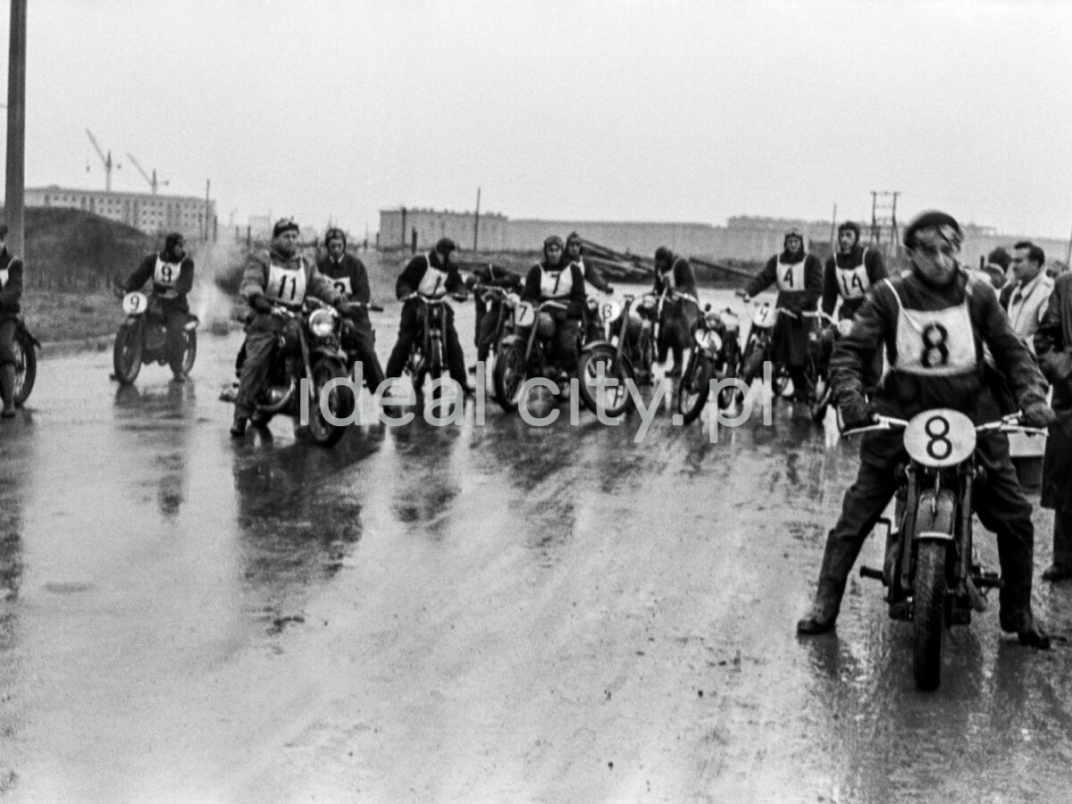 Motorcyclists in uniforms and starting numbers are getting ready to take off on wet asphalt.
