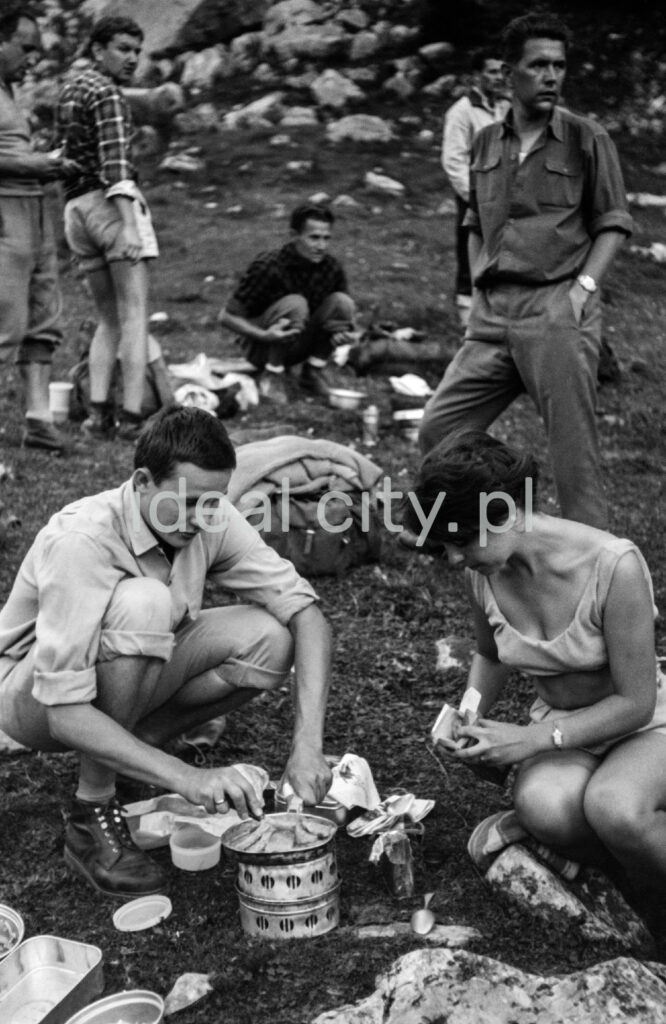 Tourists prepare a hot meal on the mountain trail.