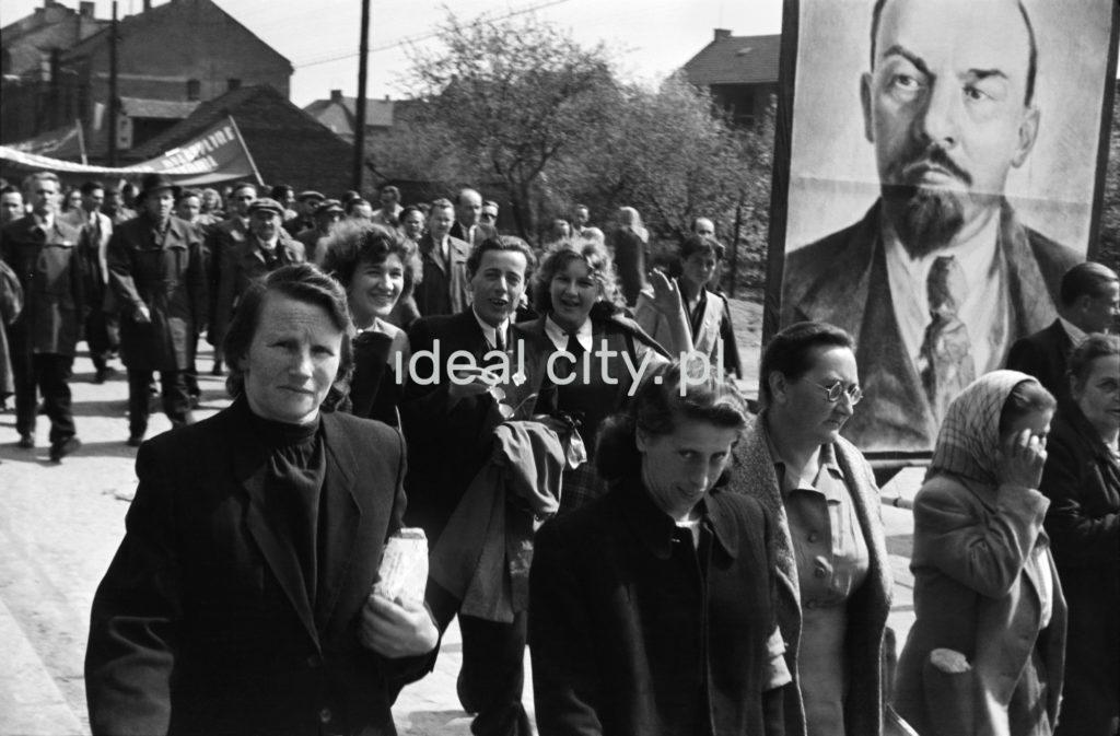 Odświętnie ubrani ludzie idą dynamicznie w pochodzie, osoby na pierwszym planie niosą portret Lenina.