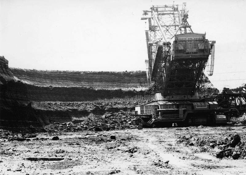 Ujęcie na potężną pogłębiarkę poszerzającą kopalnię odkrywkową, z lewej urwiste zbocze.