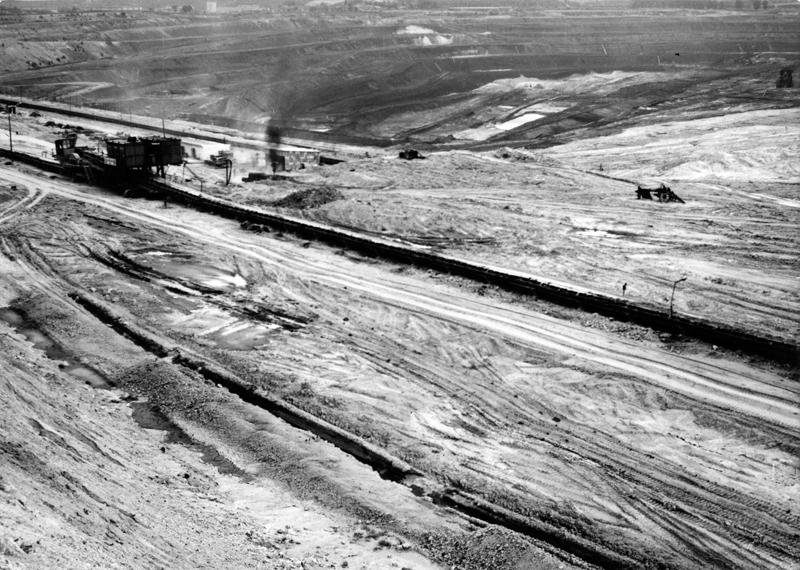 Widok z góry na torowisko kolejowe biegnące przez piaszczysty teren.