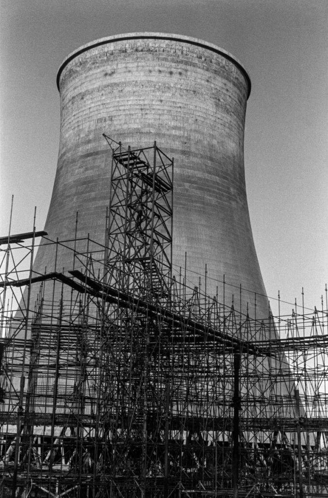 View of a cooling tower surrounded by scaffolding.