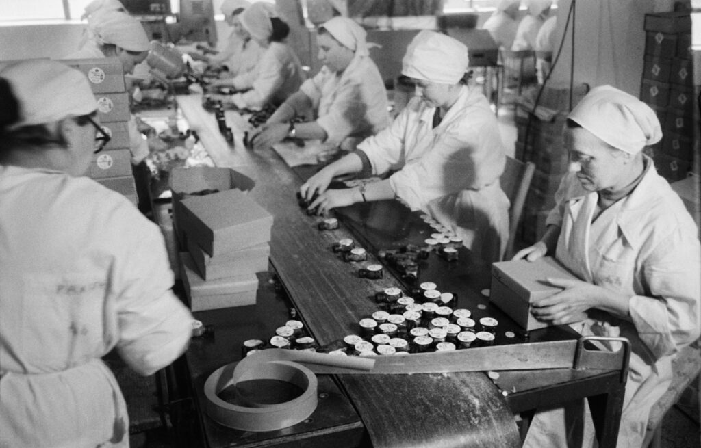 Women in aprons sitting at the table are packing pharmaceuticals
