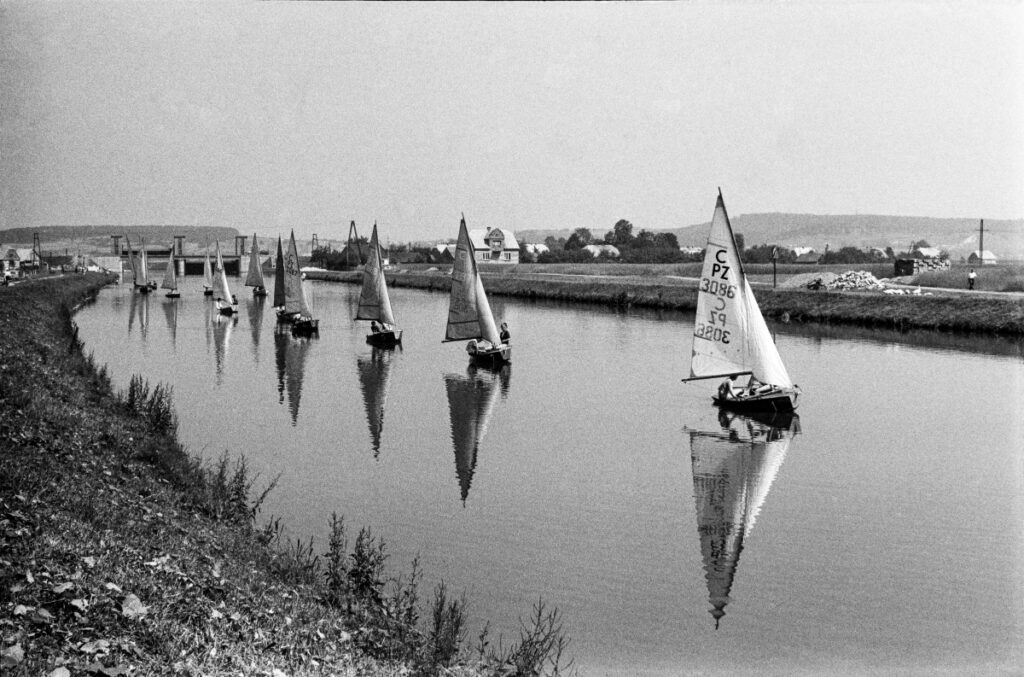 Sailboats follow the river in a row, one after the other.