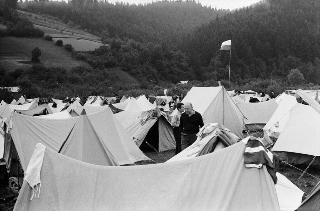 Tents fill the green valley to the horizon.