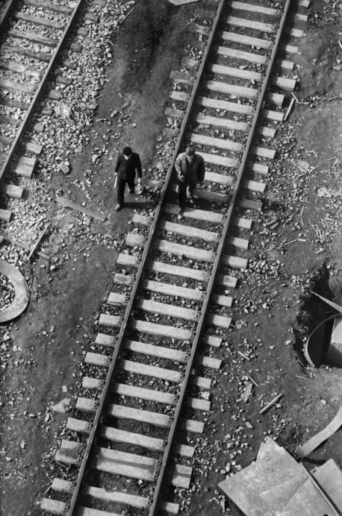Top view of men in work clothes walking on the railroad tracks.