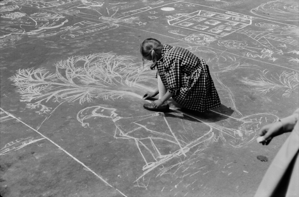 Children draw scenes related to the city and the factory with chalk on the pavement.