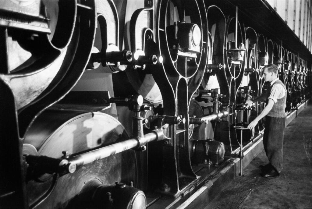 A man standing next to a huge machine regulates its work.