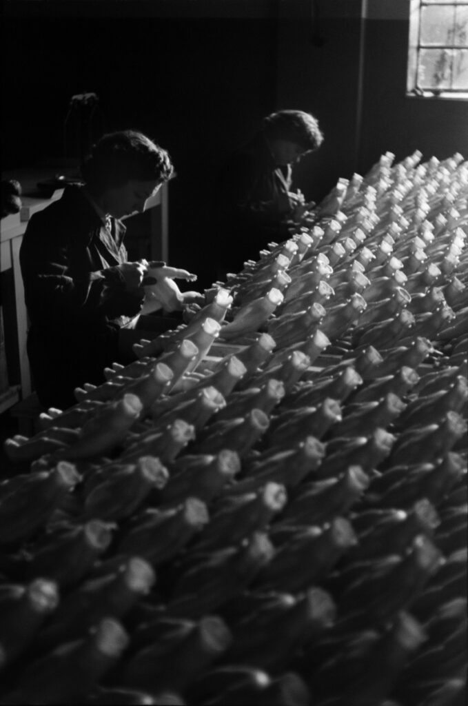 Women workers assembling doll's bodies inside production hall.