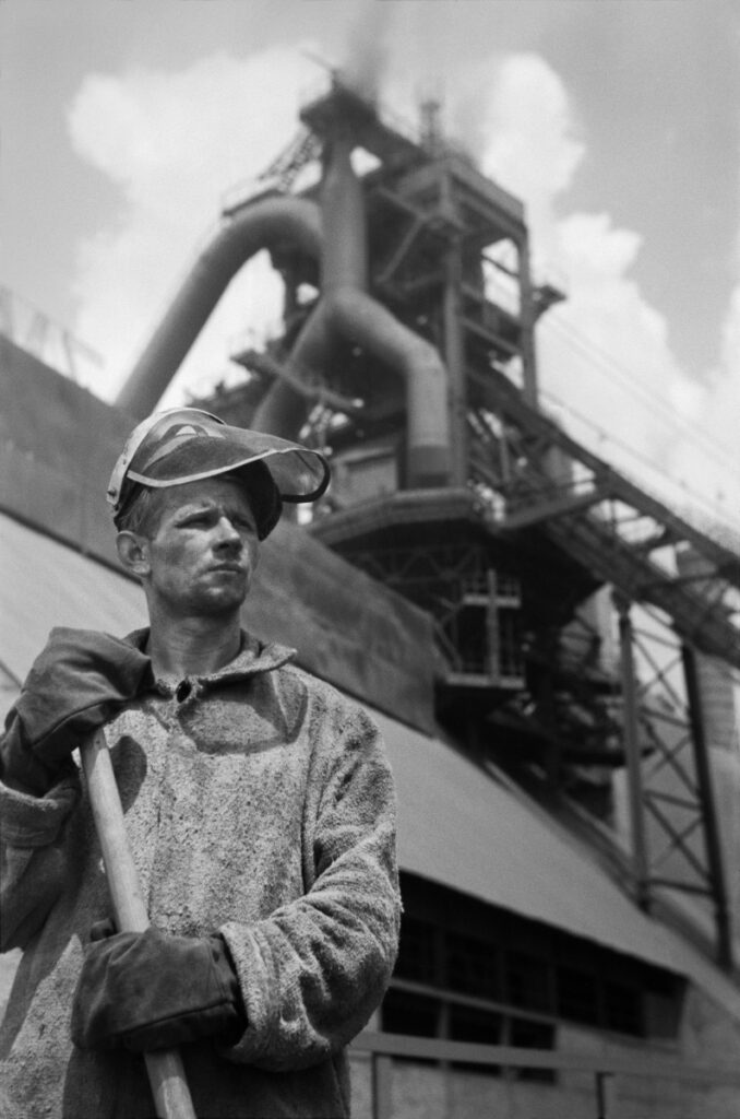 A portrait of a steelworker with work clothes in front of the steelworks building.