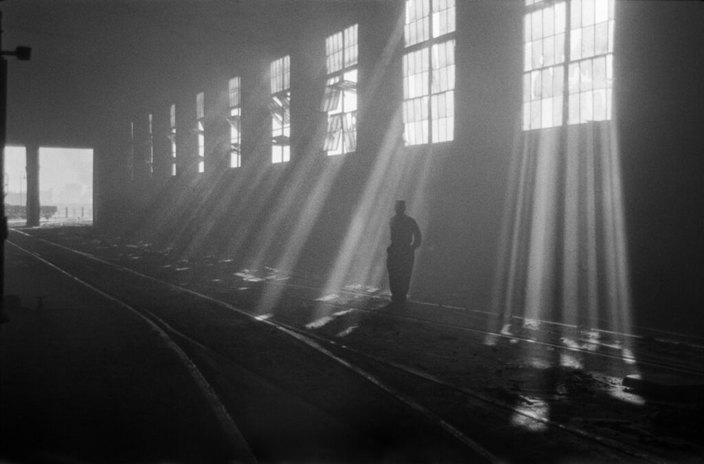 The factory hall is illuminated by streams of light, between them a figure in workwear