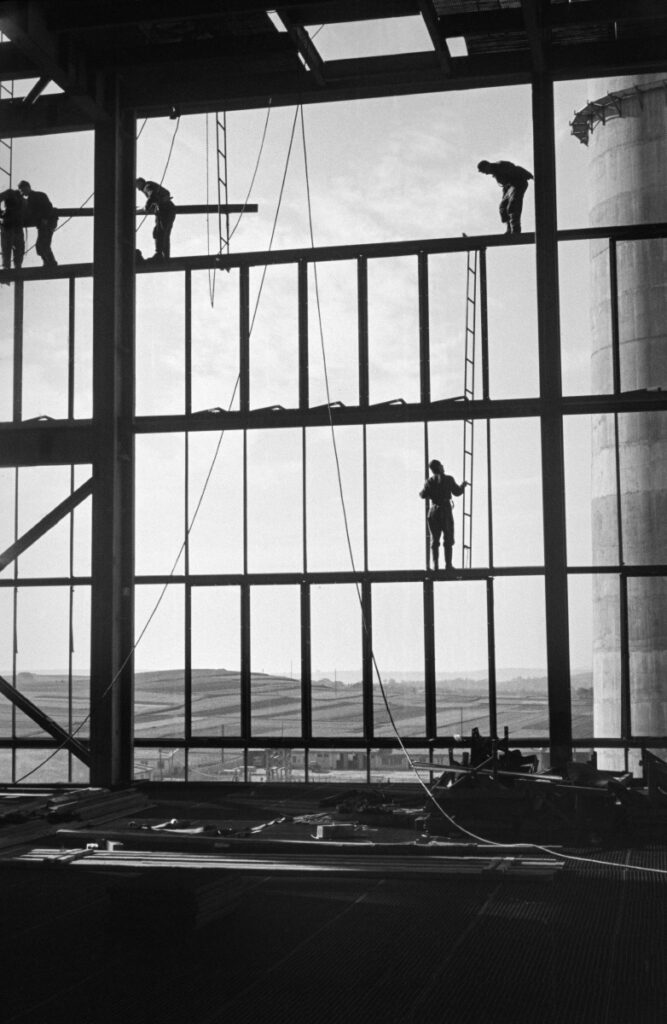 Workers on the openwork wall structure of a factory hall under construction.
