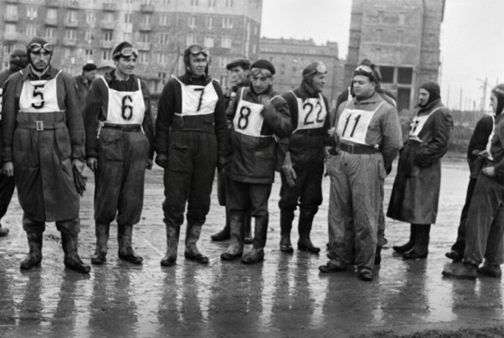 Group of people in motorcycle uniforms with number on their chests.