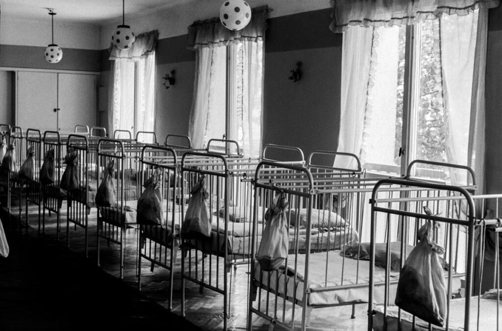 A row of hollow, made of iron children's beds, lamps in the shape of footballs under the ceiling.