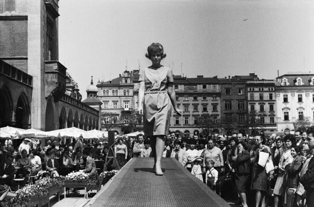 The woman marches along the catwalk set on the city square, around the crowd and tenement houses.